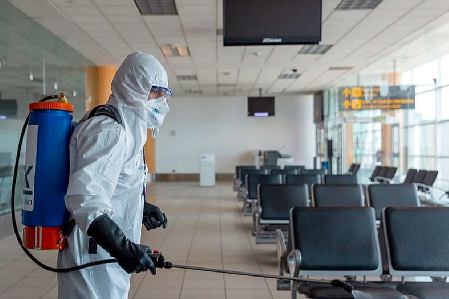 Persona realizando desinfección de instalaciones de un aeropuerto