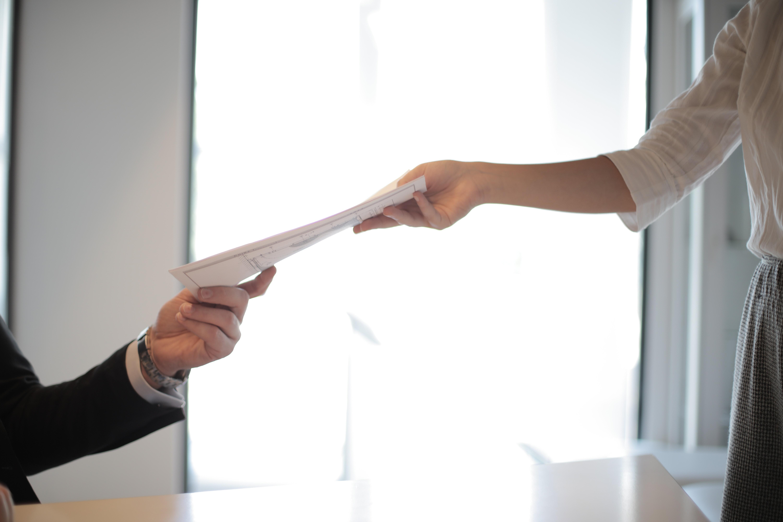 Persona entregando currículum. (Cortesía de Pexels)