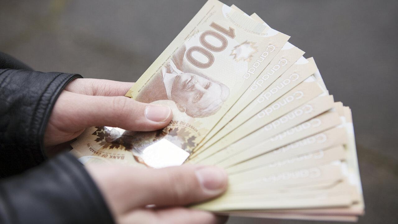 Manos sosteniendo billetes de cien dólares canadienses. (Cortesía de Fxstreet)