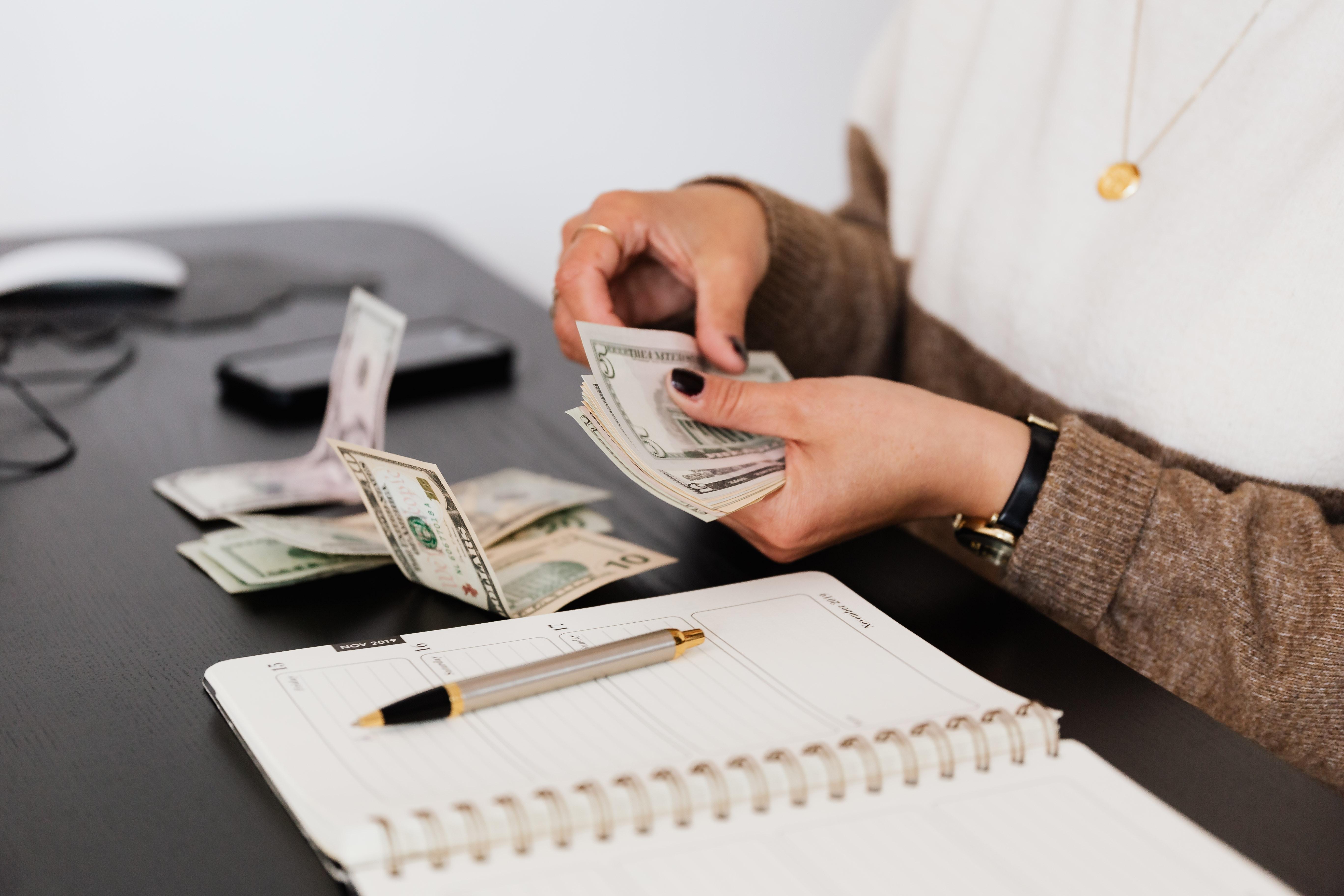 Persona contando dinero y tomando notas. (Cortesía de Pexels)